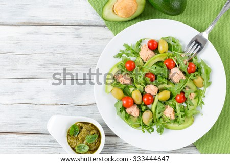 delicious tuna salad with arugula, green olives, avocado and cherry tomatoes. top view - stock photo