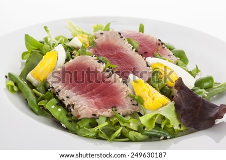 Delicious tuna steak with fresh green salad on white plate isolated on white background. Fine dining. - stock photo
