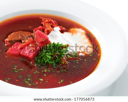 Delicious ukrainian borscht served on a white plate. Hot soup with beet and sour cream. Isolated on white. - stock photo