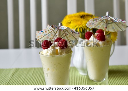 Delicious vanilla mousses topped with raspberry fruit - stock photo