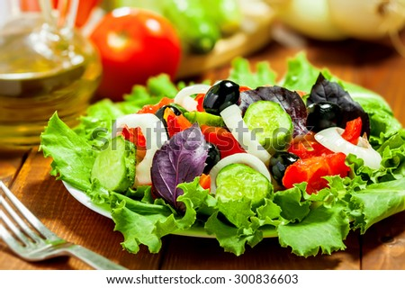 Delicious vegetable salad on table with ingredients - stock photo