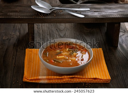 Delicious vegetable stew soup with sausage and french beans on wood. - stock photo