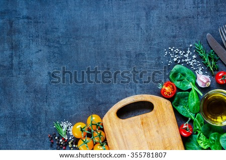 Delicious vegetables and herbs ingredients for tasty cooking around rustic wooden cutting board over dark vintage table, top view. Healthy food or vegetarian eating concept. Copy space. - stock photo