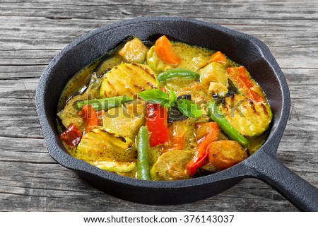 delicious vegetarian curry with vegetables stewed in a frying pan, on an old wooden table,  top view, close-up - stock photo