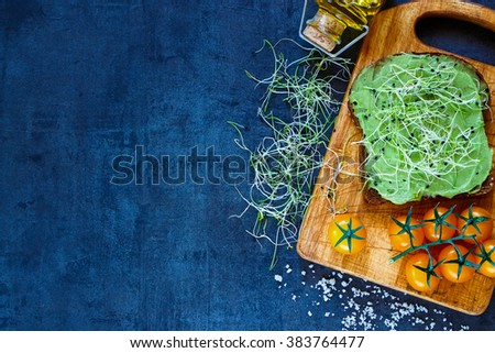 Delicious vegetarian sandwich with whole grain bread, alfalfa and guacamole on rustic wooden cutting board over dark vintage table, top view. Healthy fast food background with space for text. - stock photo