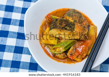 Delicious vegetarian spicy curry fish head dish on blue table cloth. - stock photo