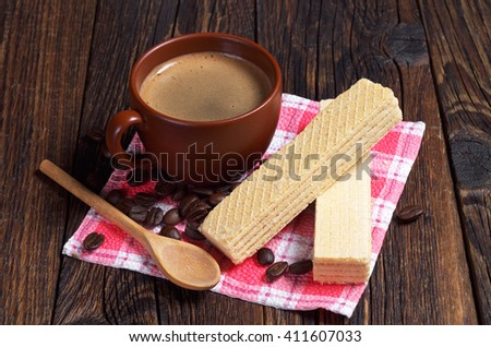 Delicious wafers and cup of hot coffee for breakfast on dark wooden table - stock photo