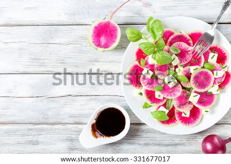 delicious watermelon radish salad with mozzarella and basil on the white platter with caramelized balsamic vinegar in the gravy boat, top view - stock photo