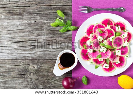 delicious watermelon radish salad with mozzarella, onion chives and basil on the white platter with caramelized balsamic vinegar in the gravy boat, view from above - stock photo