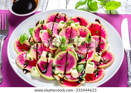 delicious watermelon radish salad with mozzarella, onion chives and basil on the white platter with caramelized balsamic vinegar in the gravy boat, selective focus, close-up - stock photo