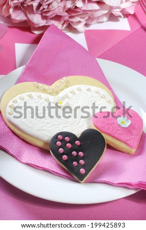 Delicious wedding party bride and groom pink, white and black heart shape biscuit cookies bridal table favors on a pink and white decorated reception table - close up. - stock photo