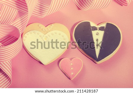 Delicious wedding party bride and groom pink, white and black heart shape biscuit cookies bridal table favors against a pink background with retro vintage filter. - stock photo