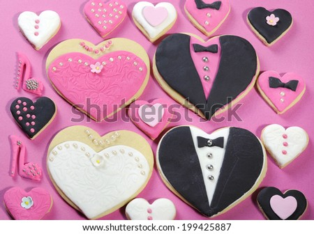 Delicious wedding party bride and groom with bridesmaid and groomsmen pink, white and black heart shape biscuit cookies bridal table favors with mini decorated hearts on a pink background. - stock photo