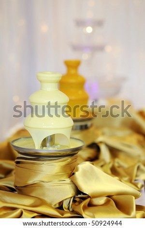 Delicious white chocolate fondue fountain on a table - stock photo