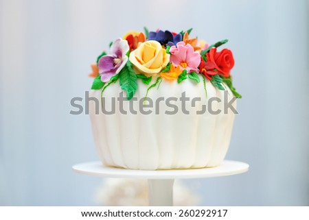Delicious white wedding or birthday cake decorated with cream colorful flowers - stock photo