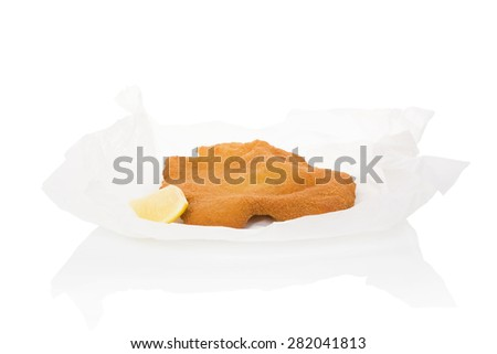Delicious wiener schnitzel on baking paper isolated on white background. Fresh modern image language. Culinary arts.  - stock photo