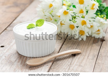 Delicious, yogurt in a ceramic bowl on wooden table. - stock photo