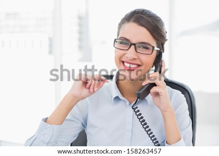Delighted classy brown haired businesswoman answering the telephone in bright office - stock photo