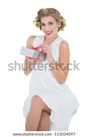 Delighted fashion blonde model opening a gift on white background - stock photo