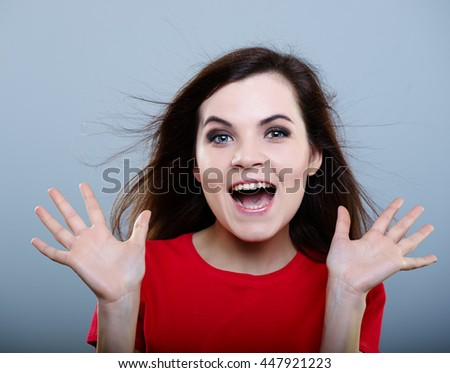 delighted girl in a red shirt with hair flying on a gray background - stock photo