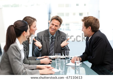 Delighted manager talking to his team at a table during a meeting - stock photo