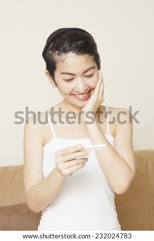 delighted young woman looking on pregnancy test - stock photo