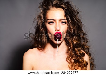 Delightsome young undressed woman with curly hair and bright pink lips holding purple round lollipop in mouth looking forward standing on grey background, horizontal picture - stock photo