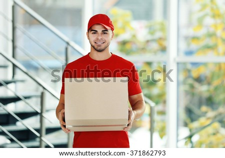 Delivery concept - postman in red uniform holding package near stairs - stock photo