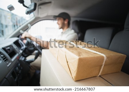 Delivery driver driving van with parcels on seat outside the warehouse - stock photo