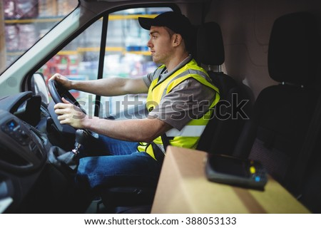 Delivery driver driving van with parcels on seat outside warehouse - stock photo