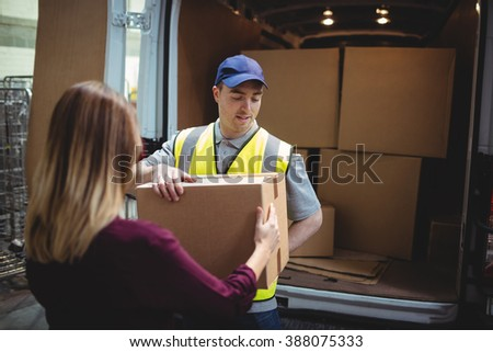 Delivery driver handing parcel to customer outside van in warehouse - stock photo
