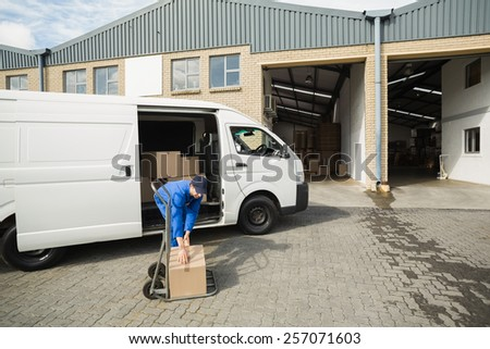 Delivery driver packing his van in a large warehouse - stock photo