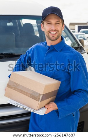Delivery driver smiling at camera by his van holding parcel outside the warehouse - stock photo