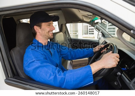 Delivery driver smiling in his van outside the warehouse - stock photo