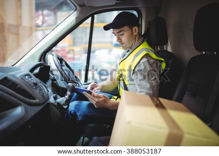 Delivery driver using tablet in van with parcels on seat outside warehouse - stock photo