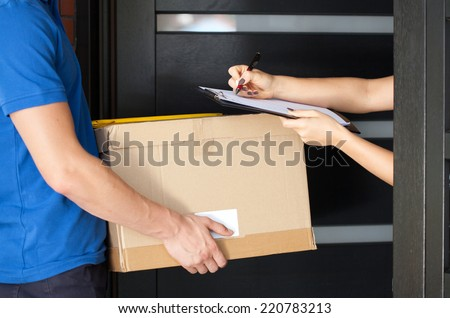 Delivery guy holding package while woman is signing documents - stock photo
