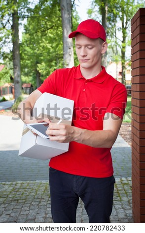 Delivery man carrying a box and looking at tablet - stock photo