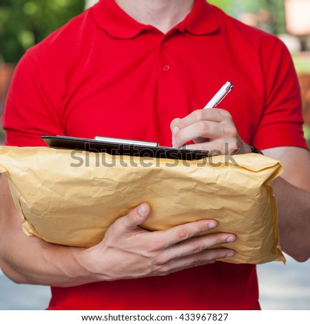 Delivery man filling in forms on parcel - stock photo