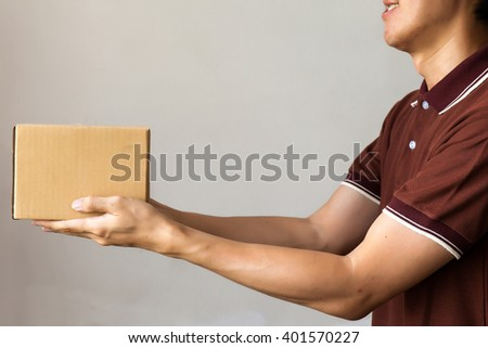 Delivery man giving a cardboard box on white background with copy space - stock photo