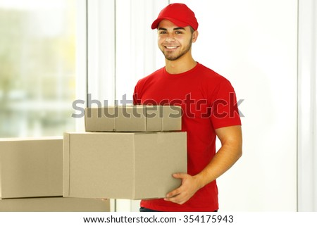 Delivery man in red uniform holding package - stock photo
