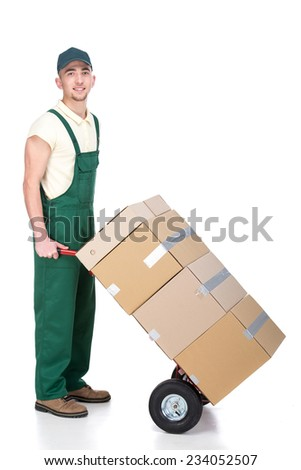 Delivery man is pushing hand truck with pile of boxes. - stock photo