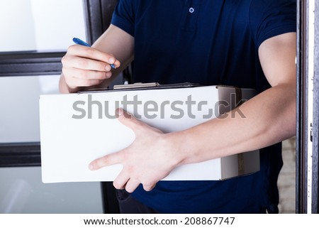Delivery man supplying pack and receiving signature - stock photo