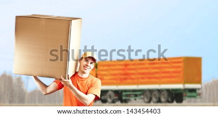 delivery man with parcel on orange truck background - stock photo