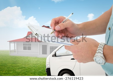Delivery man writing on clipboard against blue sky - stock photo