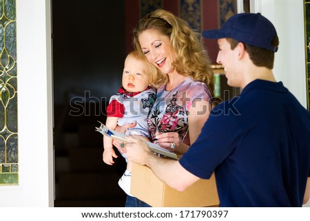 Delivery: Mother With Baby Signs For Package - stock photo
