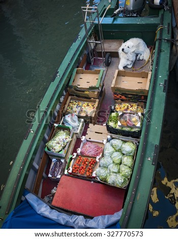 Delivery of produce in Venice by boat with dog on board. - stock photo