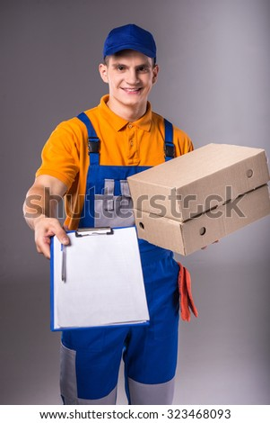 Delivery. Portrait of a young man in work clothes with boxes on a gray background - stock photo