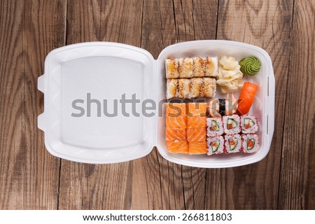 delivery service Japanese food rolls in plastic box on a wooden background - stock photo