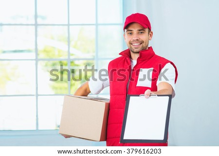 Delivery service worker in uniform delivering parcel. Man with box proposing document to sign and looking at camera - stock photo
