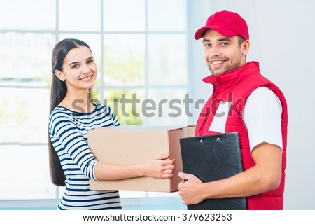 Delivery service worker in uniform delivering parcel to woman. Man with box holding document to sign and looking at camera - stock photo